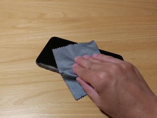 ガラスフィルム貼り付け前にiPhone 11 Pro Maxを拭いている画像