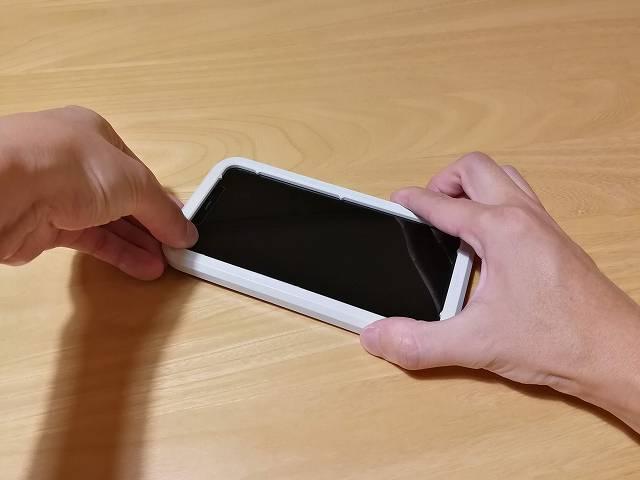 ガラスフィルムを貼り付け終わってiPhone 11 Pro Maxからガイドフレームを外している画像