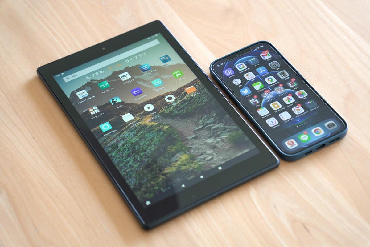 Amazon fire HD 10本体をiPhone12 Pro Maxと並べて大きさを比較している様子の画像