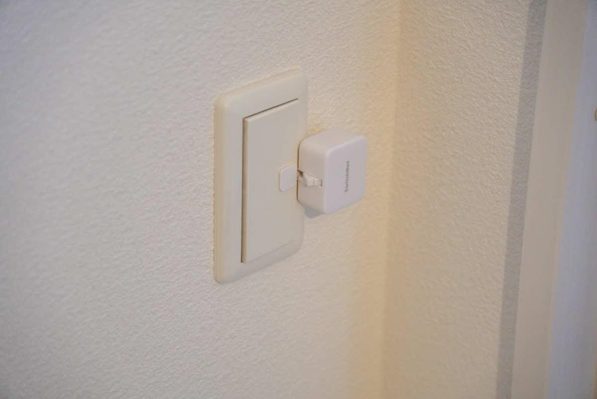 SwitchBot ボットを照明のスイッチに取り付けた様子の画像