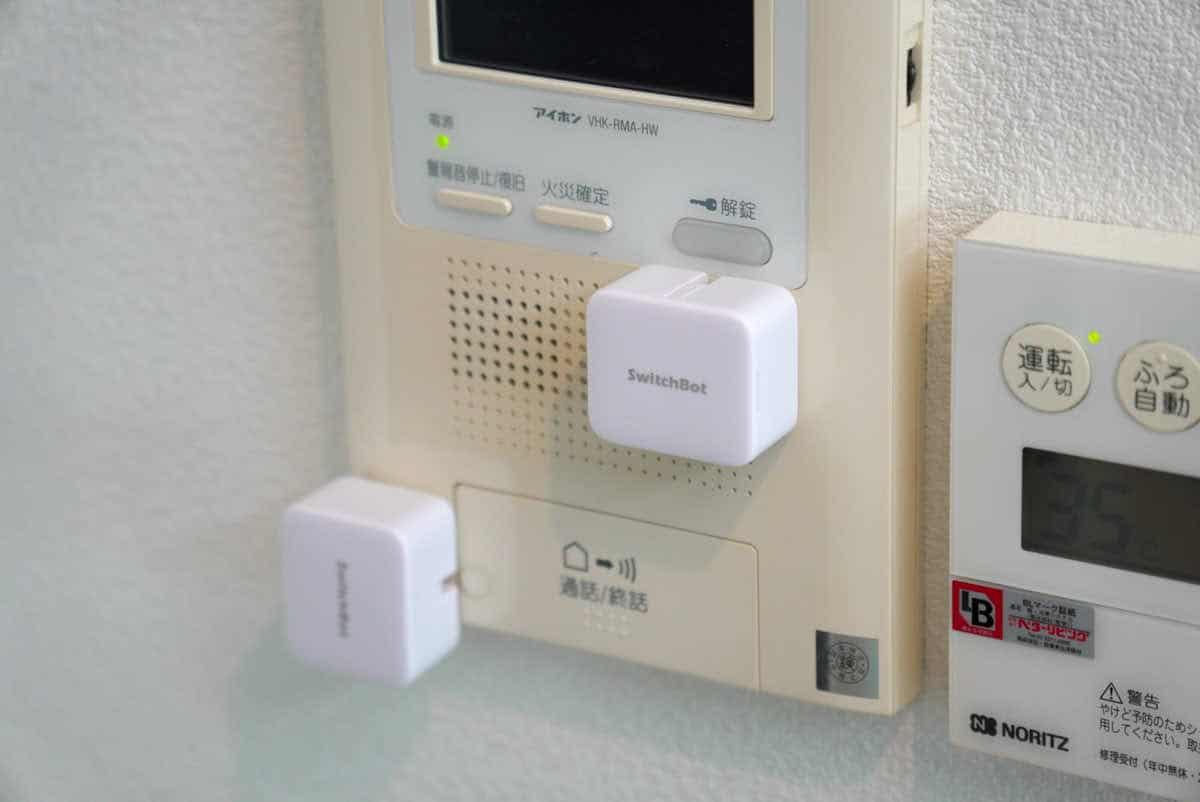 SwitchBotをインターホンに設置した様子の画像