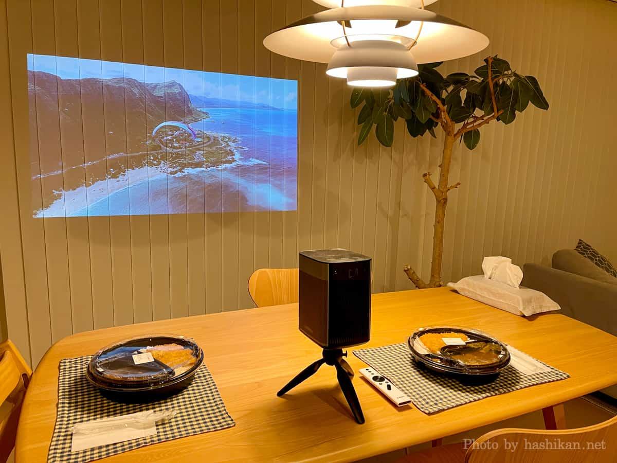 XGIMI Haloを三脚を使ってダイニングテーブルに設置しバーチカルブラインドに映像を投影している様子の画像
