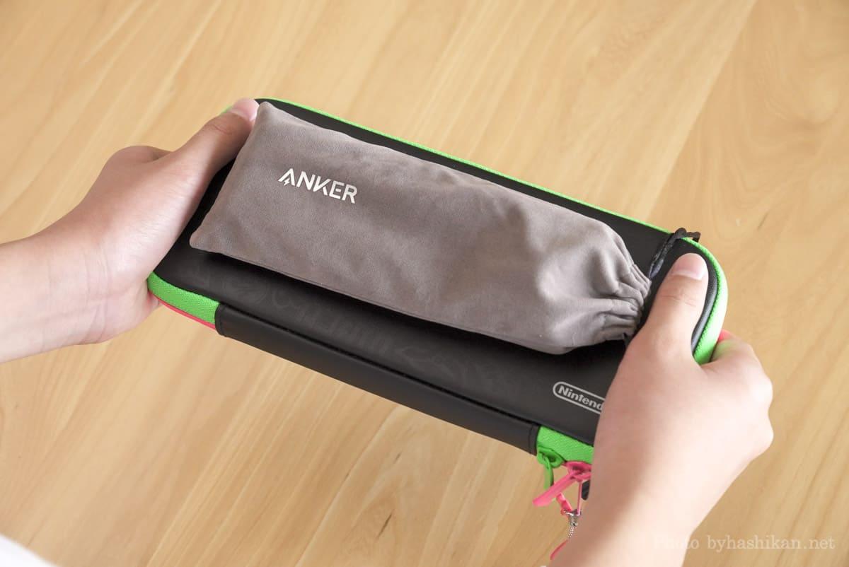 キャリングポーチに入れたAnker PowerCore 20100 Nintendo Switch Edition をケースに入れたスイッチ本体の上に載せて持っている様子の画像