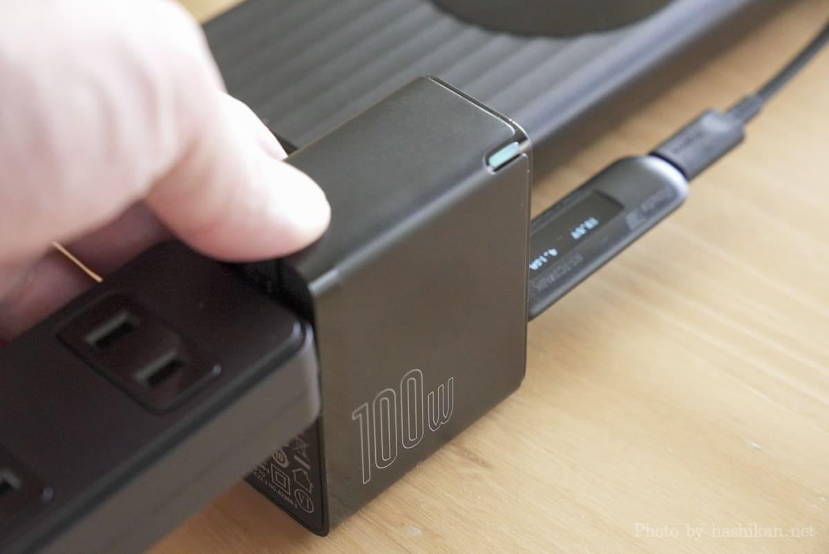 Baseus GaN2 Fast Charger で100W充電対応のモバイルバッテリーに充電したときの充電器の熱さを手で触れて確かめている様子の画像